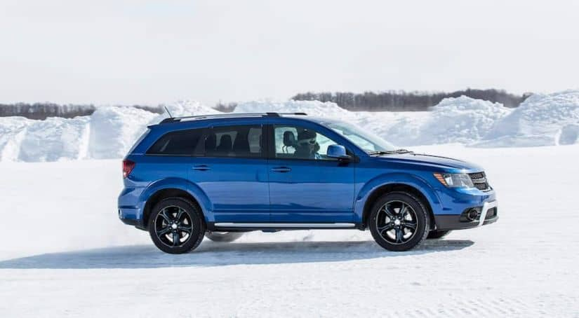 A blue 2020 used Dodge Journey is shown from the side driving through the snow.