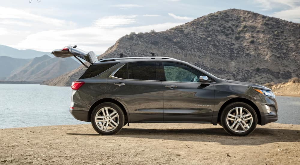 A dark grey 2021 Chevy Equinox is parked in front of a lake with the lift gate open.