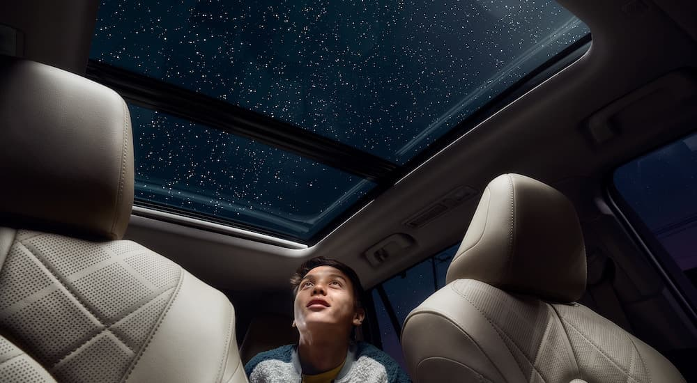 A close up shows a kid from a low angle looking out of the moonroof of a 2021 Toyota Highlander Platinum at a star filled sky.