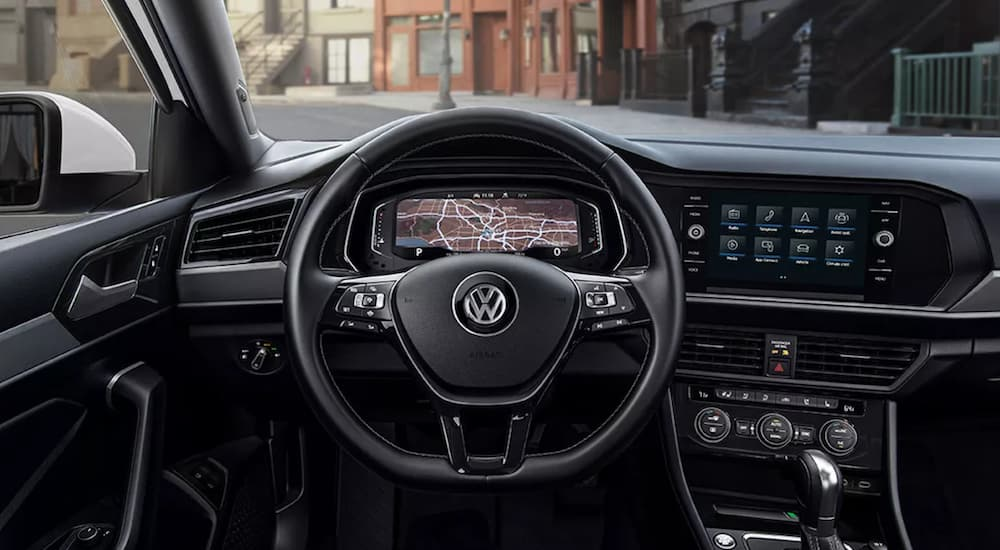 The interior of a 2021 Volkswagen Jetta shows the steering wheel and infotainment screen.