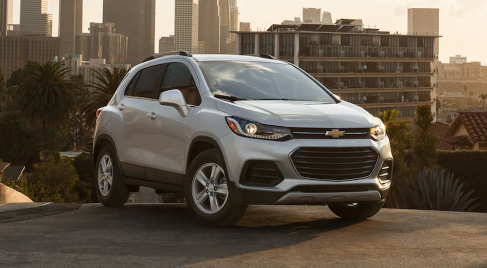 A 2021 Chevy Trax is parked in a city as sunset.