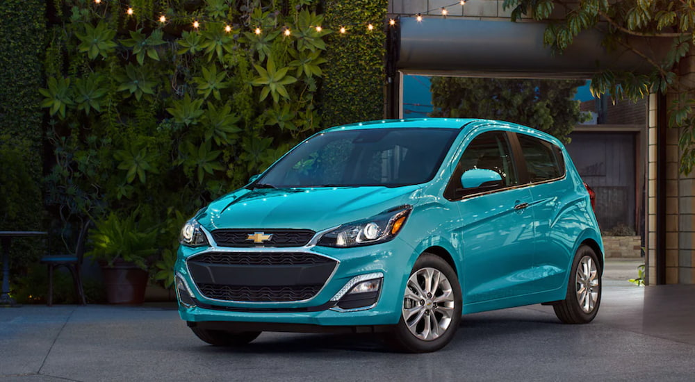 A turquoise 2021 Chevy Spark is parked outside of a house.