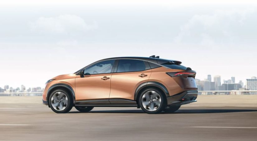 A gold 2021 Nissan Ariya is driving past a city after leaving a Nissan Dealer near you.