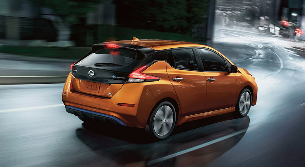 A orange 2021 Nissan Leaf is shown from an angle driving through a city at night.
