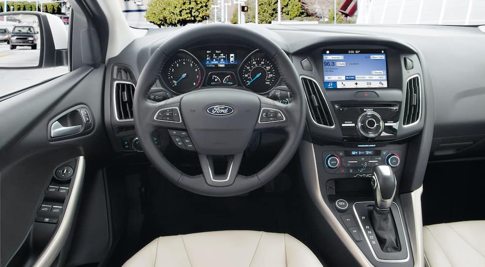 The interior of a grey 2018 Ford Focus shows the wheel and infotainment screen.
