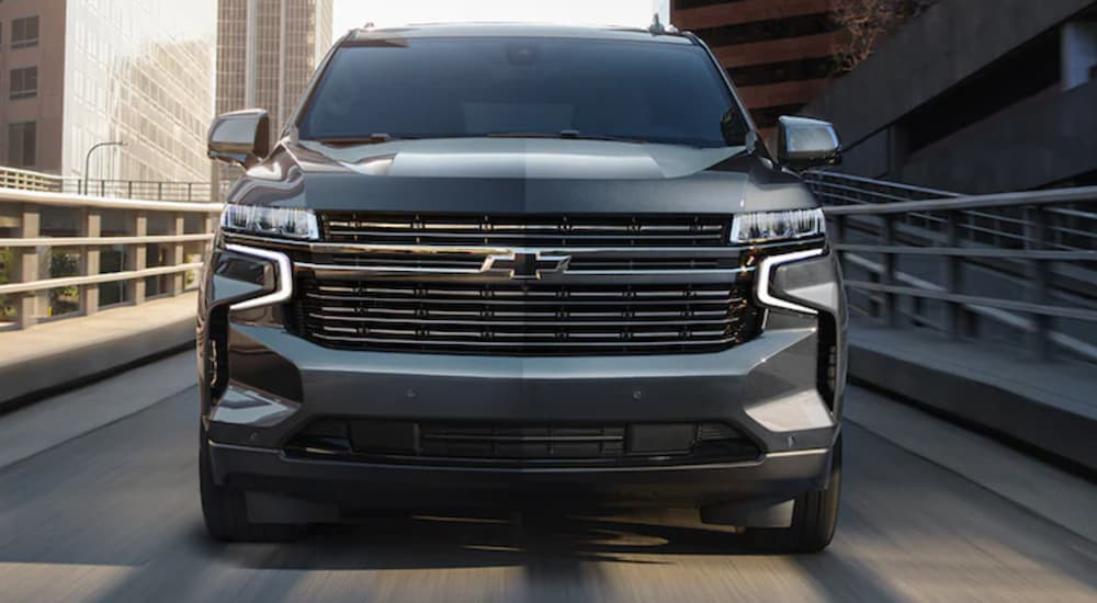 The front of a black 2021 Chevy Tahoe is shown from the front driving on an off-ramp.