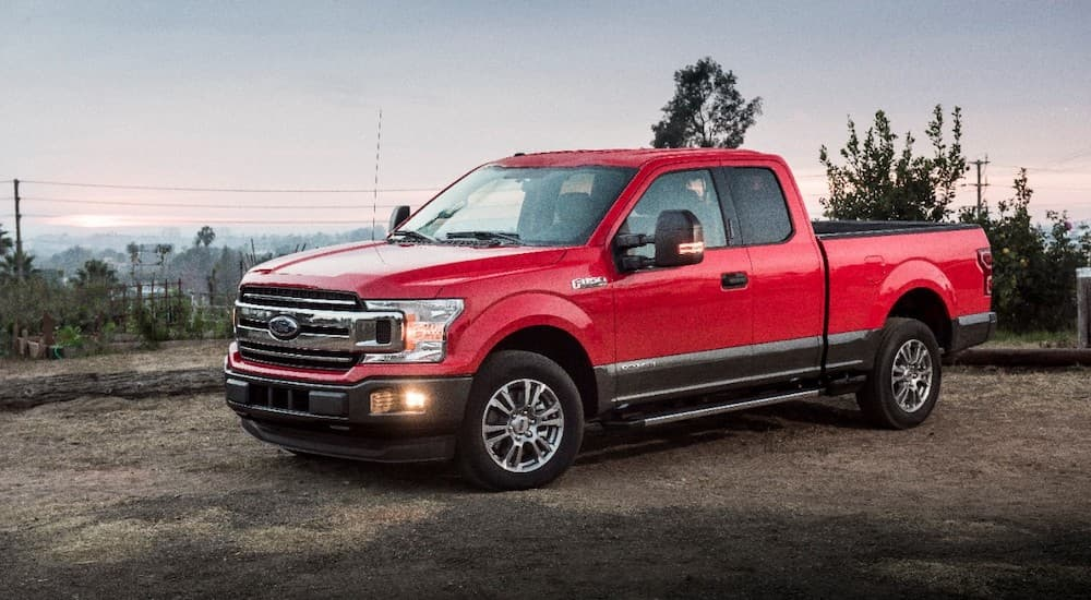 A red 2018 Ford F-150 is shown from the side parked on the dirt.