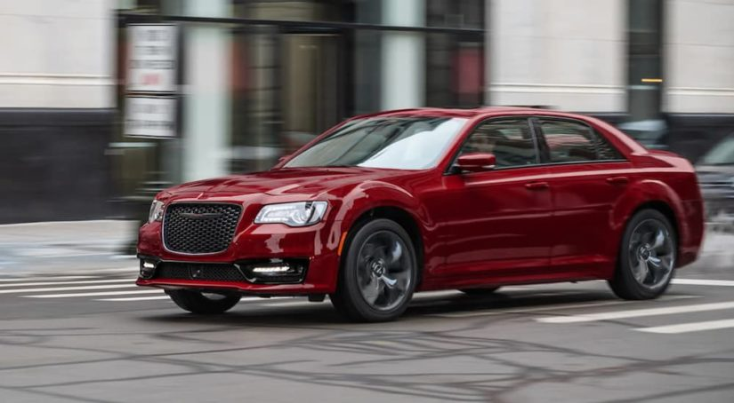 A red 2021 Chrysler 300 is shown from the side driving through a city.