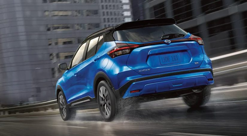A blue 2021 Nissan Kicks is shown from the rear driving through a city.
