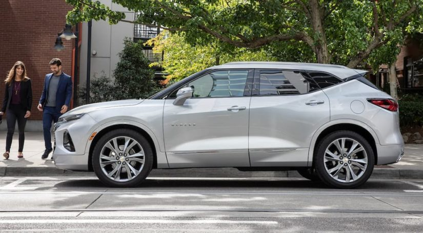 A white 2022 Chevy Blazer is shown from the side parked in front of a brick building.