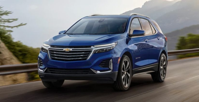A blue 2022 Chevy Equinox is shown from the front driving past a mountain range.