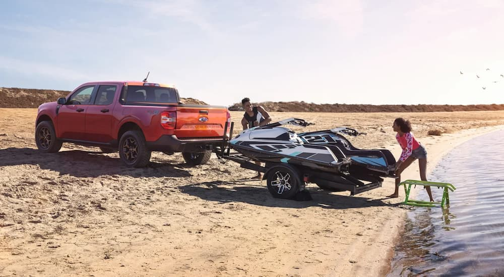 An orange 2022 Ford Maverick is shown towing a jet-ski next to the ocean.