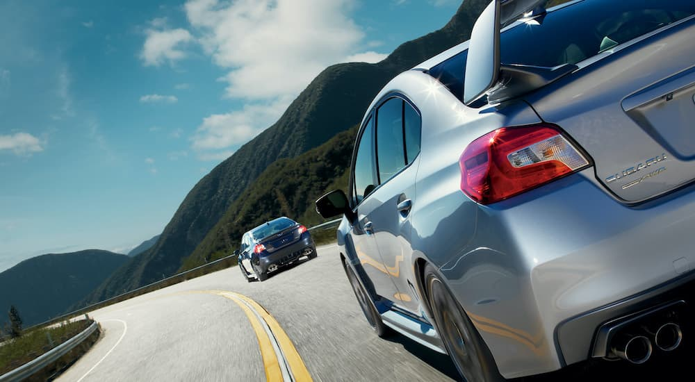 A blue 2021 Subaru WRX is shown being followed by a silver 2021 STI after visiting a car dealership.