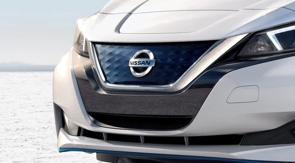 A white 2021 Nissan LEAF shows the grille in close up.