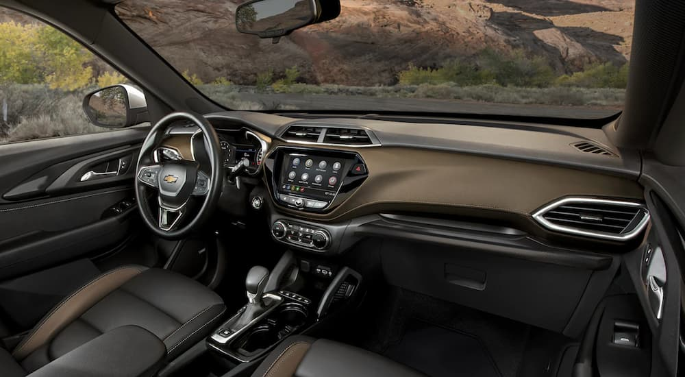 The black and gold interior of. 2022 Chevy Trailblazer shows the steering wheel and infotainment screen.