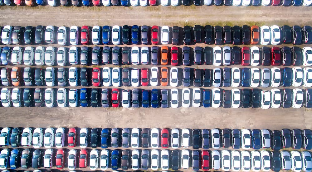 A lot full of used cars are shown from above at at used car dealer.