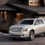 A light colored 2019 GMC Yukon XL Denali is parked in front of a modern house.